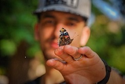 man with butterfly on tip of finger