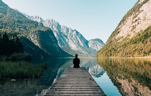 Man sitting on bridge meditating near mountain scene